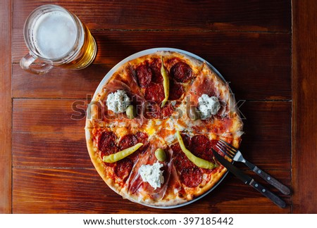 Top view of delicious Domestic Pizza and Beer Mug on wooden table. Ingredients peeled tomato, cheese, sausage, ham, sour cream, egg, pepperoni, olives, oregano. - stock photo