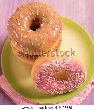top view of delicious donuts with icing on green plate  - stock photo