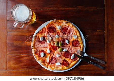 Top view of delicious specialty of the house Pizza and Beer Mug on wooden table. Ingredients peeled tomato, cheese, ham, sausage, feta cheese, olives, oregano. - stock photo