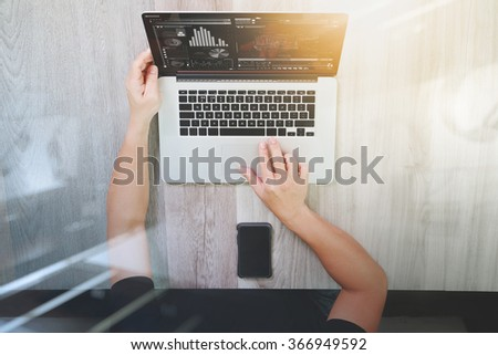 top view of Designer hand working with laptop computer and smart phone and digital tablet on wooden desk as responsive web design concept - stock photo