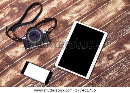 Top view of diverse equipment for photographer on wooden background - stock photo