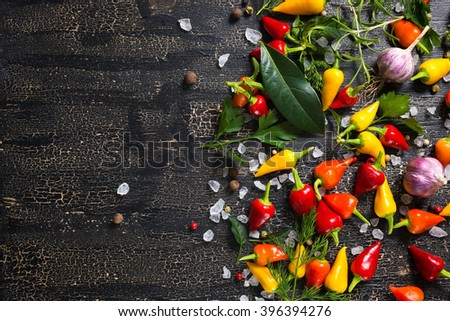 top view of dry and red peppers, sea salt, different greenery on cracks black background   - stock photo