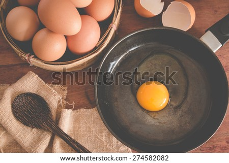 top view of egg and Broken egg with frying pan on wood table - stock photo