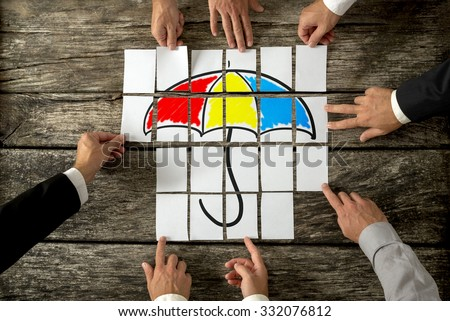Top view of eight male hands assembling a colourful umbrella with cards over textured rustic desk. Conceptual of safety, shelter and insurance. - stock photo