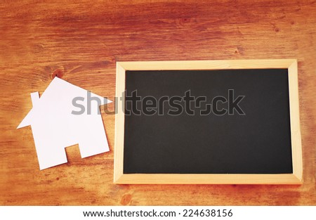 top view of empty blackboard with room for text and house shaped paper cut over wooden table - stock photo