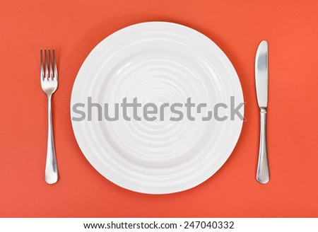 top view of empty white plate with fork and knife set on red background - stock photo