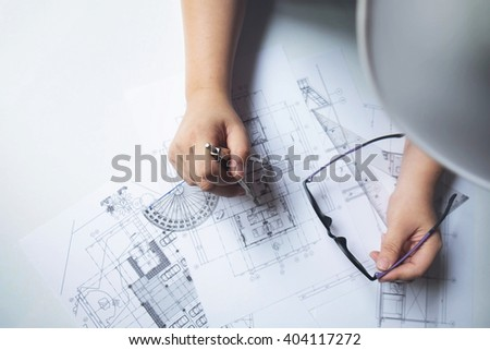 Top view of engineer hand sketching a construction project with Pencil, compass. - stock photo