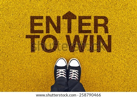 Top view of Enter To Win Concept on Asphalt Road, Man standing Above the Title Ready to Walk. - stock photo