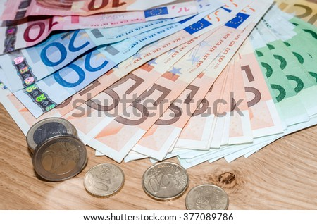 Top view of Euro coins and banknotes  on wooden table