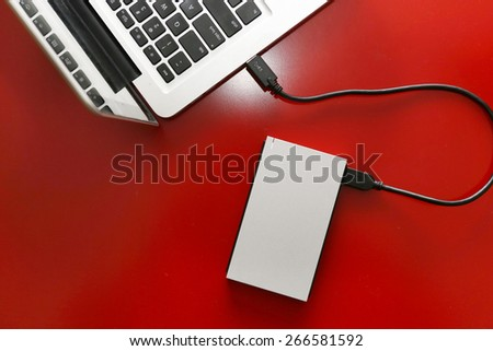 top view of external hard drive connected to laptop on the red table - stock photo