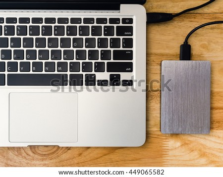 Top view of external or portable hard drive (HDD) connected to laptop computer for transfer or backup data on wooden texture office desktop - stock photo