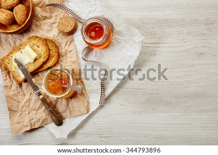 Top view of farm breakfast set with honey, toasts with butter, walnuts, apricot jam in jar - stock photo