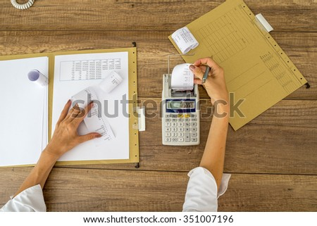 Top view of female accountant making calculations using adding machine with folders, documents and receipts on her office workdesk. - stock photo