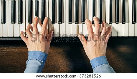 top view of female hands playing the piano  - stock photo
