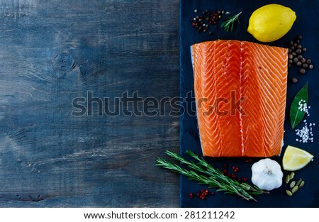 Top view of Fillet Salmon with aromatic spices and lemon on slate texture. Seafood on dark wooden background with space for text. Vegetarian food, health or cooking concept. - stock photo