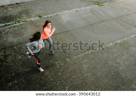 Top view of fitness female athletes running on rainy day. Women working out Friends training together and talking to each other. - stock photo