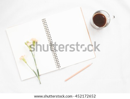 Top view of flower on blank notebook on white fabric workspace background. - stock photo