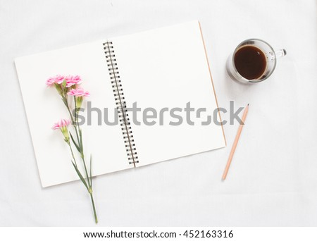 Top view of flowers on blank notebook on white fabric workspace background. - stock photo