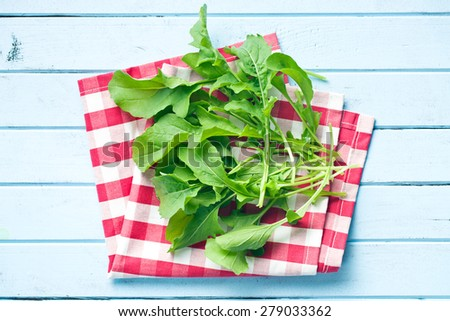 top view of fresh arugula leaves on kitchen table - stock photo
