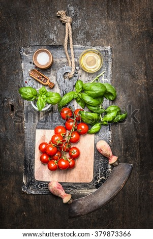 Top view of  fresh cherry tomatoes with basil and olive oil on rustic background. Ingredients for tasty Italian food. - stock photo