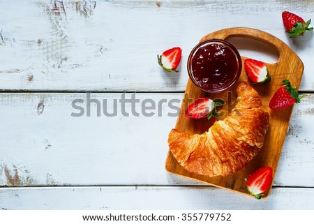Top view of fresh croissant, fruity jam and ripe berries on vintage rustic chopping board over white wooden background with space for text. Breakfast concept. - stock photo