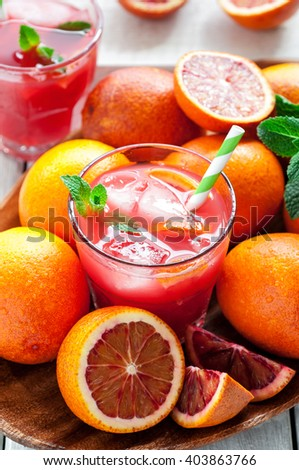 Top view of fresh delicious juice with red oranges on white wooden background, selective focus, vertical