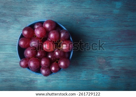 Top view of fresh grapes in blue plate on wooden table - stock photo