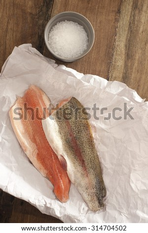 Top View of Fresh Rainbow Trout Meat on a Paper Placed on Wooden Table with Rock Salt on a Saucer. - stock photo