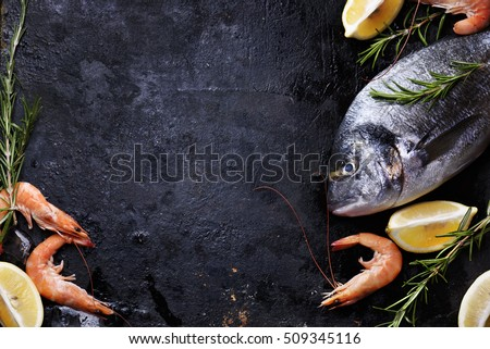 Top view of fresh sea food on grunge textured black background. Shrimps, bream, herbs, lemon and ice on slate with copyspace.