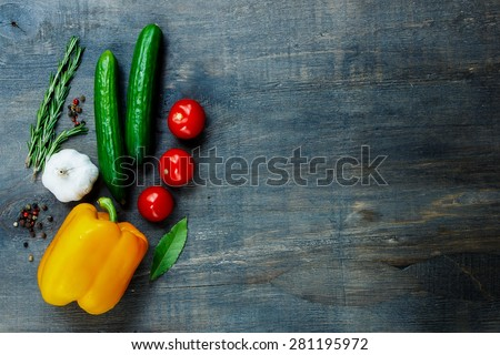 Top view of fresh vegetables and spices on dark wooden background with space for text. Vegetarian food, health or cooking concept. - stock photo