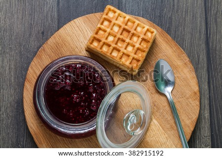top view of fruity jam with spoon and homemade waffles on a wooden table and cutting board - stock photo