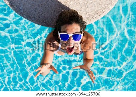Top view of funny expressive woman gesturing enjoying summer vacation in resort swimming pool. Beautiful brunette girl wearing sunglasses and having fun on summertime. - stock photo