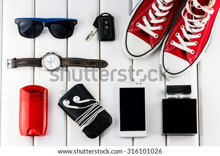 Top view of gentlemanly set: red shoes, car keys, sunglasses, watch, smartphone, player, stick antiperspirant and perfume on white wooden background - stock photo