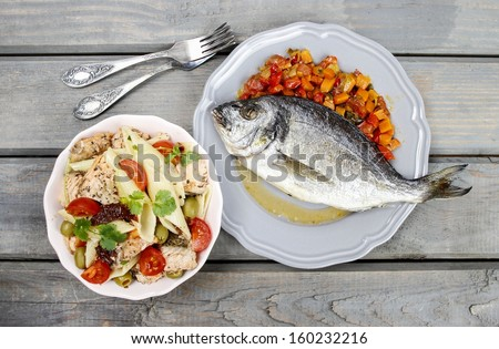 Top view of gilt-head bream fish and salmon salad on wooden background. Symbol of healthy living.  - stock photo