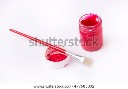 Top view of glass jar with red paint and brush on dirty cork isolated on white background