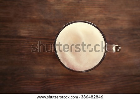 Top view of glass with light beer on wooden background - stock photo