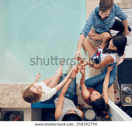 Top view of group of friends toasting at party by a swimming pool. High angle shot of young people sitting by the pool having wine. Men and women partying by the pool. - stock photo