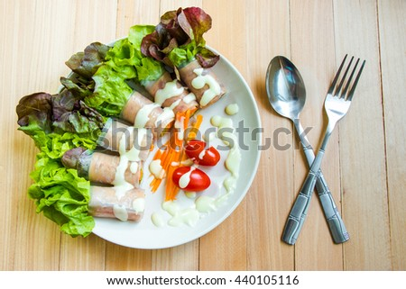 Top view of Ham roll  salad with lettuce, tomato, egg and cream sauce, put near Spoon and fork. clean food and fresh vegetable. - stock photo
