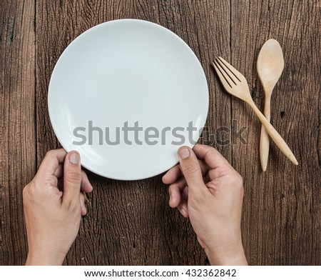 Top view of hand hold a empty dish(plate) with spoon on wood