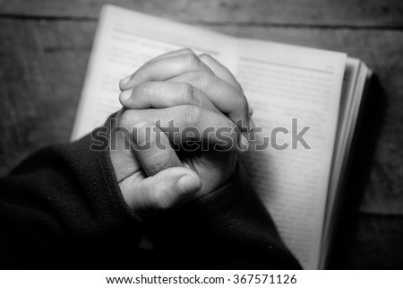 Top view of hands praying with a bible in a dark over wooden table. Black and White effected photo. - stock photo