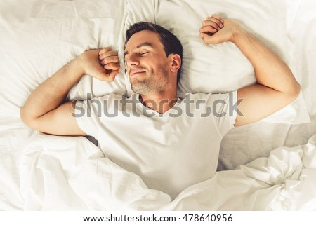 Top view of handsome man smiling while sleeping in his bed at home