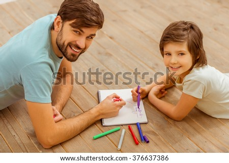 Top view of handsome young father and his cute little son drawing, looking in camera and smiling while lying on a wooden floor in the room - stock photo