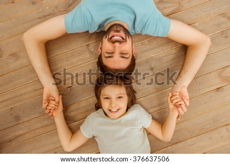 Top view of handsome young father and his cute little son lying head to head on a wooden floor and holding hands - stock photo