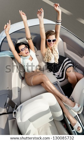 Top view of happy women in sunglasses with their hands up sit in the cabriolet - stock photo