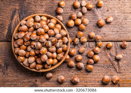 Top view of hazelnuts in a wooden bowl - stock photo