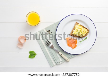 Top view of healthy breakfast with scrambled eggs on toast, smoked salmon, fresh orange juice and green salad - stock photo