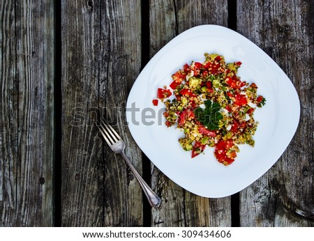 Top view of healthy salad with avocado, quinoa and fresh vegetables on rustic wooden background. Vegetarian food and health concept. - stock photo