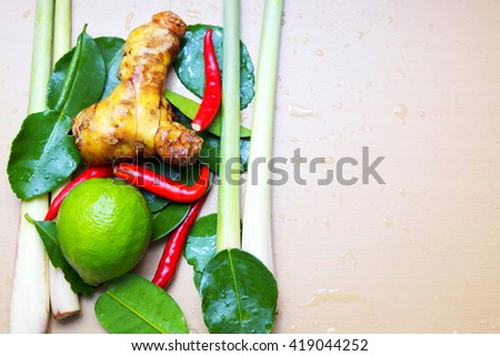 Top view of herb ingredients with drops of water of Tom Yum spicy Traditional Thai food cuisine on wooden background. - stock photo