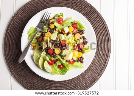 Top view of homemade southwest black bean lime salad with corn, cherry tomatoes, lettuce, avocado, and black beans with vinaigrette dressing for clean eating on brown place mat  - stock photo