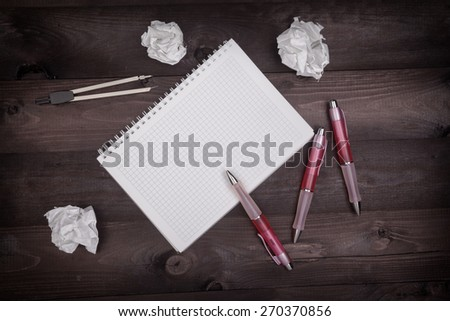 Top view of idea concept with pencils, notepad and crumpled paper on a black wooden table - stock photo